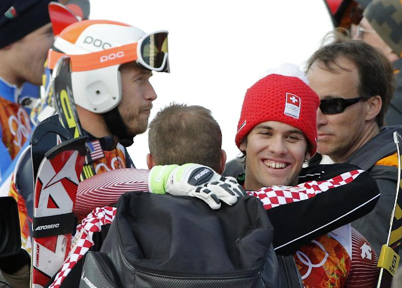 Men's supercombined gold medalist, Switzerland's Sandro Viletta, right, embraces another athlete as United States' Bode Miller, left, stands nearby in the finish area of the Alpine ski venue at the Sochi 2014 Winter Olympics, Friday, Feb. 14, 2014, in Krasnaya Polyana, Russia. (AP Photo/Christophe Ena)