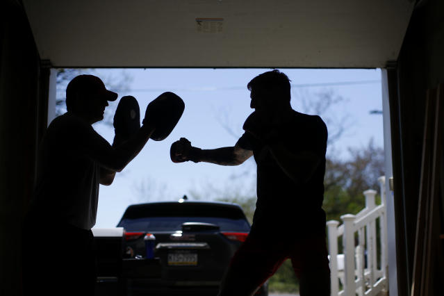 Fighter Kyle Daukaus, right, trains with his brother, Chris Daukaus, in their garage, Saturday, May 2, 2020, in Philadelphia. Kyle, a rising star in the regional MMA promotion Cage Fury Fighting Championships, is still chasing his dream of getting the call to fight for UFC despite the coronavirus pandemic. (AP Photo/Matt Slocum)