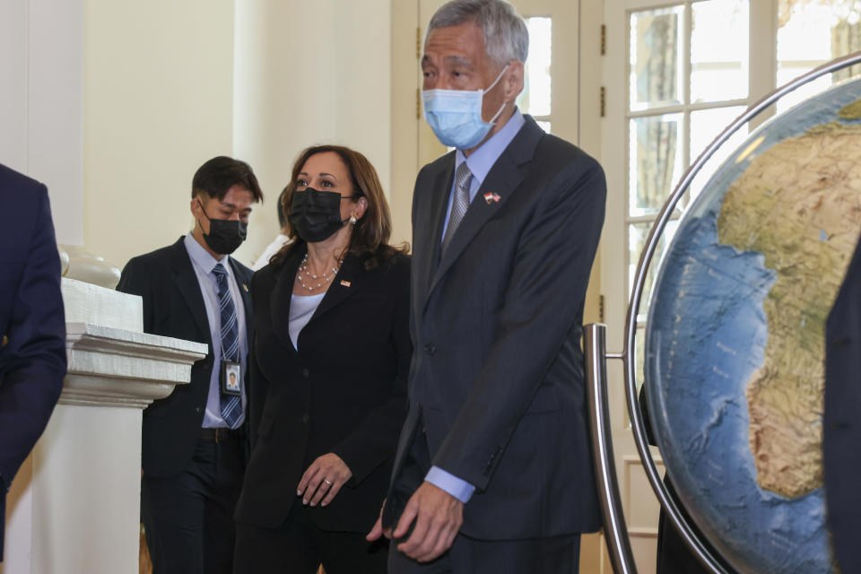 U.S. Vice President Kamala Harris, center, walks with Singapore's Prime Minister Lee Hsien Loong, right, to a bilateral meeting at the Istana in Singapore Monday, Aug. 23, 2021. (Evelyn Hockstein/Pool Photo via AP)