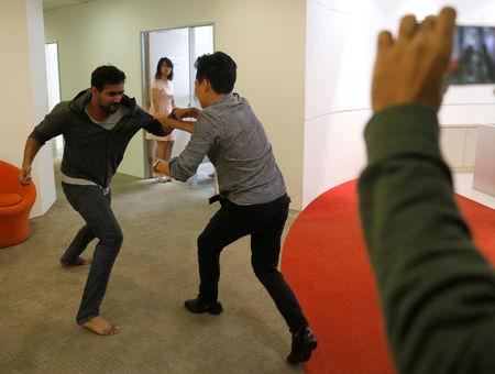 "Graymatics employees pretend to fight as they record footage to be used to ""train"" their software to watch and filter internet videos for violence, at their office in Singapore"