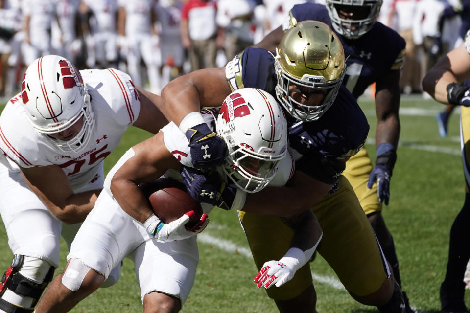 Notre Dame defensive lineman Howard Cross III, right, tackles Wisconsin running back Chez Mellusi for a loss during the first half of an NCAA college football game Saturday, Sept. 25, 2021, in Chicago. (AP Photo/Charles Rex Arbogast)