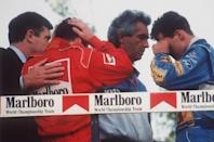 FILE - In this May 01, 1994, file photo, Italy's Nicola Larini, left, holds his head and Germany's Michael Schumacher, right, wipes a tear from his eyes while talking with Benetton director-general Flavio Briatore, center, on the podium following the San Marino Formula One Grand Prix crash in Imola, Italy. The drivers were reacting to the news that the Brazilian driver Ayrton Senna was in critical condition at a Bologna hospital after a crash in the race. Later it was announced that Senna had died after suffering severe head injuries. Schumacher won the race and Larini finished second. Despite his career being cut short when he was 34, his 41 wins stand third all-time behind Michael Schumacher's 91 and rival Alain Prost's 51. Senna died at the 1994 San Marino Grand Prix. (AP-Photo/Claudio Luffoli, File)