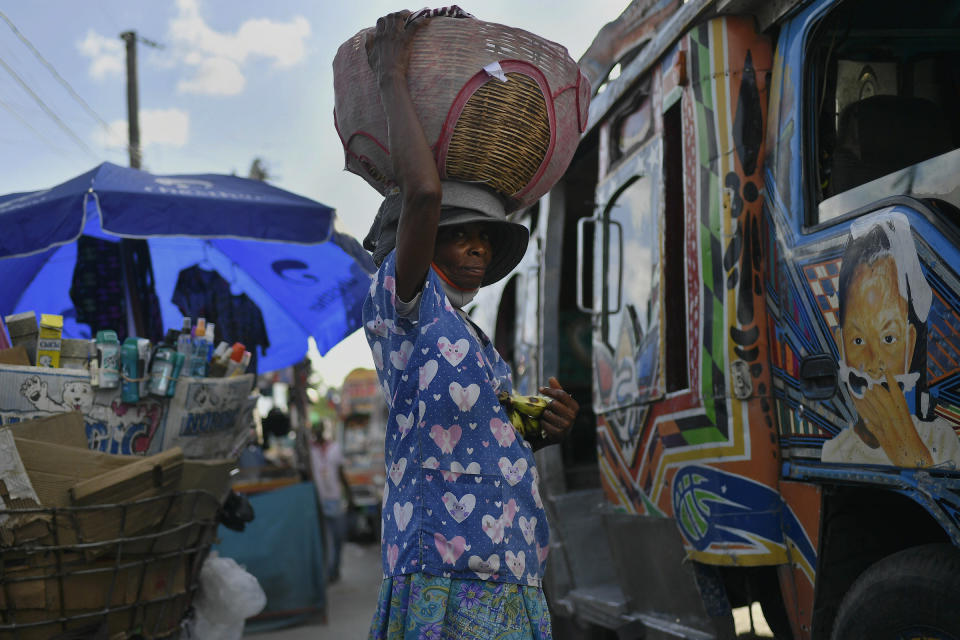 A street vendor hawking bananas waits for customers at a bus terminal in Port-au-Prince, Haiti, Saturday, July 10, 2021, three days after President Jovenel Moise was assassinated in his home. (AP Photo /Matias Delacroix)