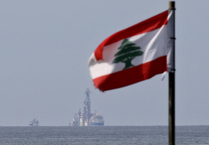"""A Lebanese flag flutters in the wind as the drilling ship Tungsten Explorer is seen off the coast of Beirut, Lebanon, Thursday, Feb. 27, 2020. Lebanon's president on Thursday inaugurated Lebanon's first offshore exploratory drilling for oil and gas, calling it a """"historic day"""" for the cash-strapped country. (AP Photo/Hussein Malla)"""