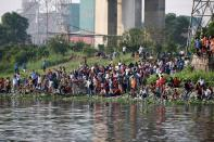 Relatives and onlookers look on after several people died when a ferry collided with a cargo vessel and sank on Sunday in the Shitalakhsyaa River in Narayanganj