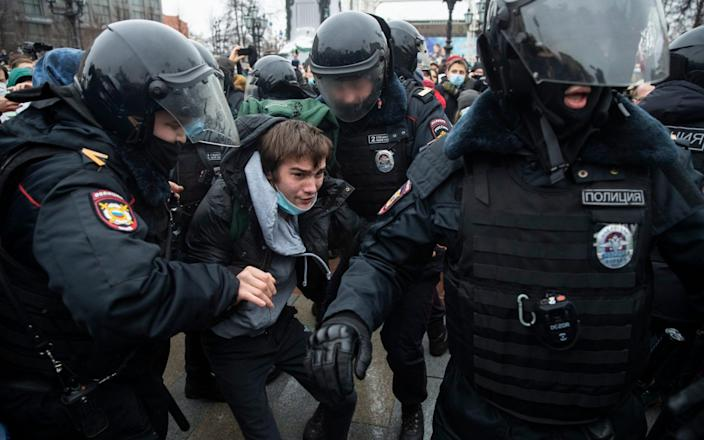Police officers detain a man during a protest against the jailing of Mr Navalny on January 23 - Pavel Golovkin/AP