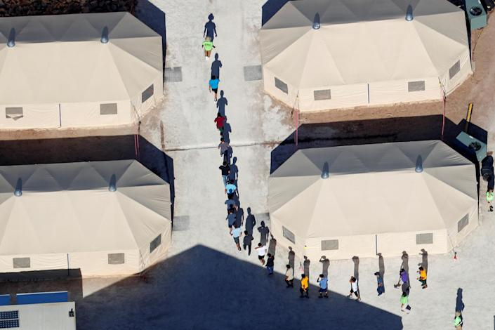 """<p>Immigrant children, many of whom have been separated from their parents under a new """"zero tolerance"""" policy by the Trump administration, walk in single file between tents in their compound next to the Mexican border in Tornillo, Texas, June 18, 2018. (Photo: Mike Blake/Reuters) </p>"""
