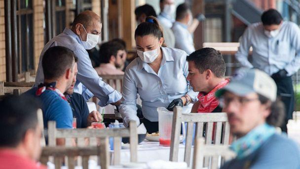 PHOTO: A waiter wearing a mask and gloves delivers food to a table to customers seated at an outdoor patio at a Mexican restaurant in Washington, D.C., May 29, 2020. (Saul Loeb/AFP via Getty Images)