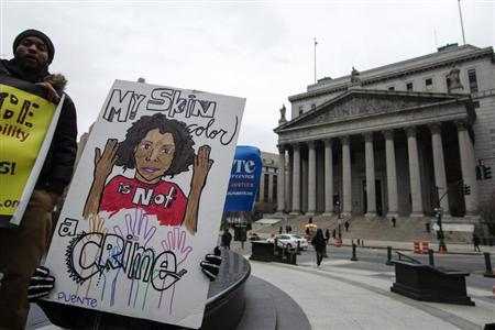 """Demonstrators hold signs protesting the NYPD's """"stop and frisk"""" crime-fighting tactic outside of Manhattan Federal Court in New York"""