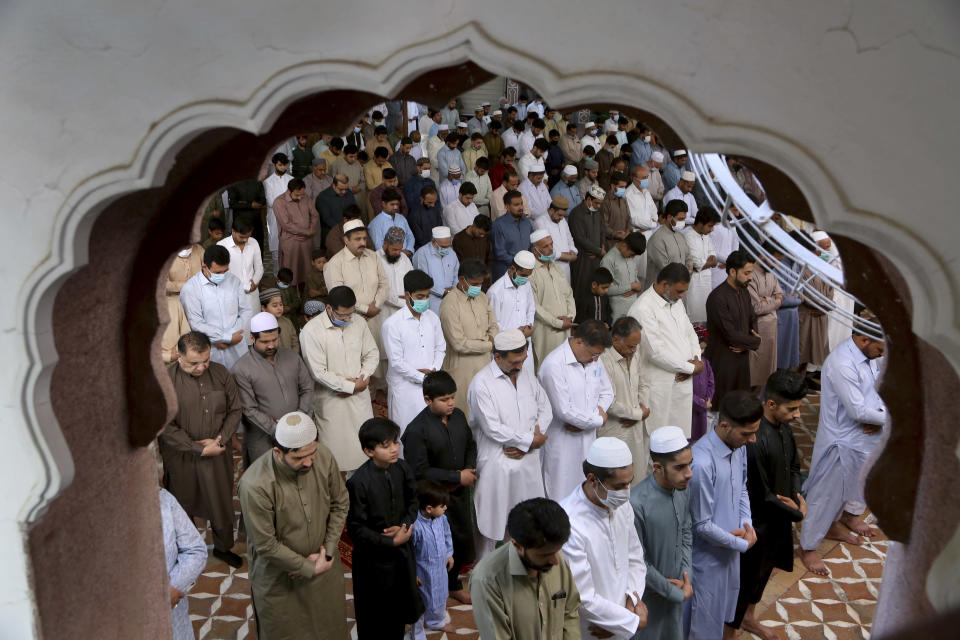 Muslims perform an Eid al-Fitr prayer at a mosque, in Peshawar, Pakistan, Thursday, May 13, 2021. Millions of Muslims across the world are marking a muted and gloomy holiday of Eid al-Fitr, the end of the fasting month of Ramadan, a usually joyous three-day celebration that has been significantly toned down as coronavirus cases soar. (AP Photo/Muhammad Sajjad)