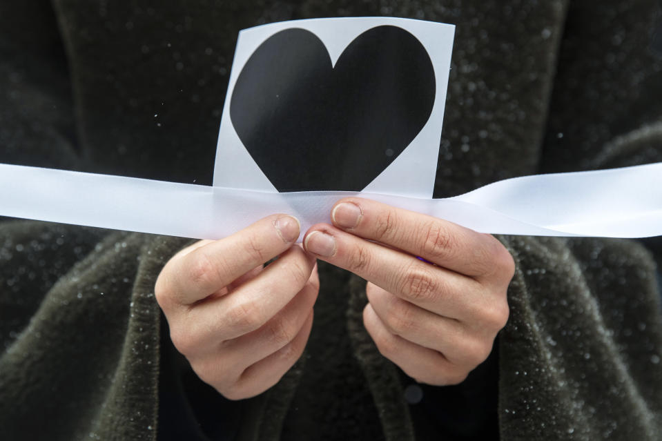A woman holds an image of heart and a white ribbon as she stands in a line of women during a rally in support of jailed opposition leader Alexei Navalny, and his wife Yulia Navalnaya at Arbat street in Moscow, Russia, Sunday, Feb. 14, 2021. The weekend protests in scores of cities last month over Navalny's detention represented the largest outpouring of popular discontent in years and appeared to have rattled the Kremlin. (AP Photo/Pavel Golovkin)