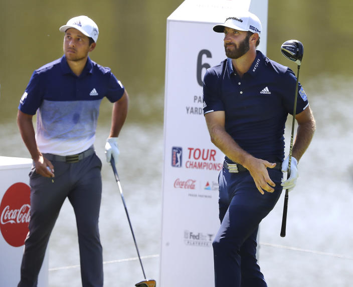 Dustin Johnson, right, watches after teeing off on the sixth hole on his way to a birdie as Xander Schauffele looks on during the final round of the Tour Championship golf tournament at East Lake Golf Club, Monday, Sept. 7, 2020, in Atlanta. (Curtis Compton/Atlanta Journal-Constitution via AP)