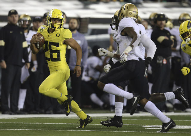 Oregon's Travis Dye, left, breaks for a big gain against Colorado in the fourth quarter of an NCAA college football game Friday, Oct. 11, 2019, in Eugene, Ore. (AP Photo/Chris Pietsch)