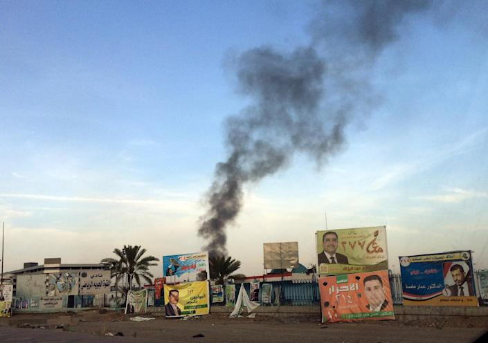 FILE - In this file photo taken Friday, April 25, 2014, smoke rises above campaign posters after a series of bombs that exploded at a campaign rally for a Shiite group in Baghdad, Iraq, ahead of the country's parliamentary election. As parliamentary elections are held Wednesday, April 30, more than two years after the withdrawal of U.S. troops, Baghdad is once again a city gripped by fear and scarred by violence. (AP Photo/Karim Kadim, File)