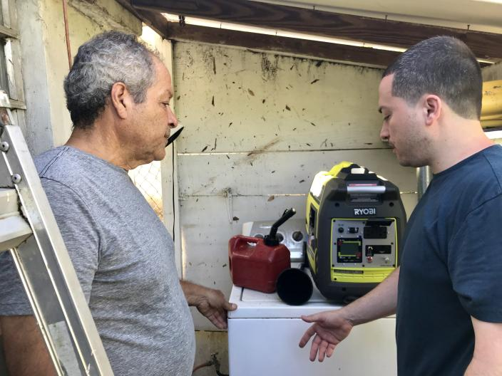 Jesse Vazquez, left, and his son debate where to keep the generator outside their house in Bayamon, Puerto Rico. (Photo: Caitlin Dickson/Yahoo News)