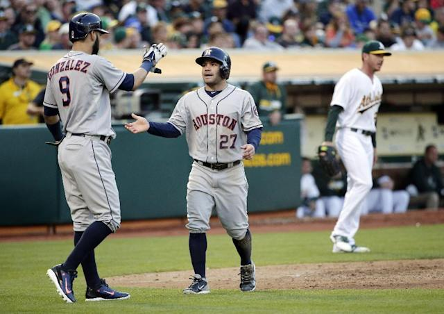 Houston Astros' Jose Altuve (27) celebrates with teammate Marwin Gonzalez (9) after they both scored on a single from Chris Carter during the third inning of a baseball game against the Oakland Athletics on Tuesday, July 22, 2014, in Oakland, Calif. (AP Photo)