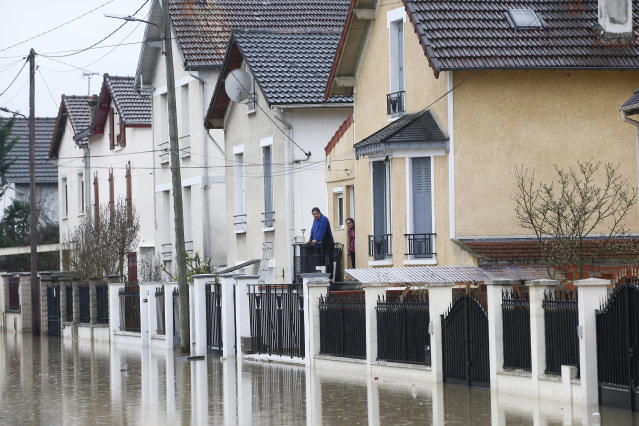 <p>People watch a flooded street of Villeneuve-Saint-Georges, outside Paris, where the Yerres river flooded on Thursday, Jan.25, 2018. (Photo: Thibault Camus/AP) </p>