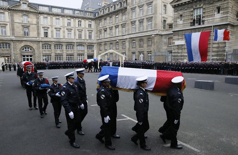Police carry the coffins of the three officers killed in the French Islamist attacks in a ceremony in Paris on January 13, 2015 (AFP Photo/Patrick Kovarik)