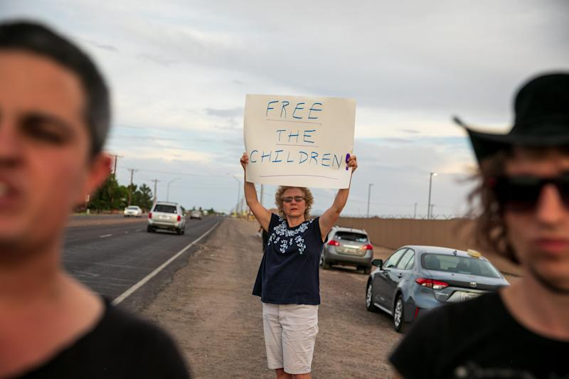 Sue Saunders from Marin County, California, holds a sign in front of the Clint, Texas, facility on July 4, 2019.