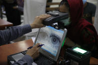 FILE - In this June 30, 2021, file photo an employee scans the eyes of a woman for biometric data needed to apply for a passport, at the passport office in Kabul, Afghanistan. Over two decades, the United States and its allies spent hundreds of millions of dollars building databases for the Afghan people. The nobly stated goal was to promote law and order and government accountability, and to modernize a war-ravaged land. But in the Taliban's lightning seizure of power, most of that digital apparatus fell into the hands of an unreliable rulers. Built with few data-protection safeguards, it risks becoming the high-tech jackboots of a surveillance state. (AP Photo/Rahmat Gul, File)