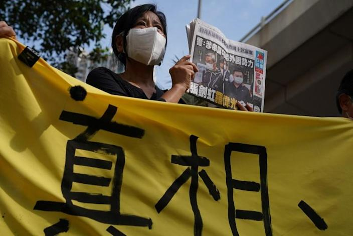 A supporter holds a copy of Apple Daily newspaper during a court hearing outside West Magistrates' Courts, after police charge two executives of the pro-democracy Apple Daily newspaper over the national security law, in Hong Kong