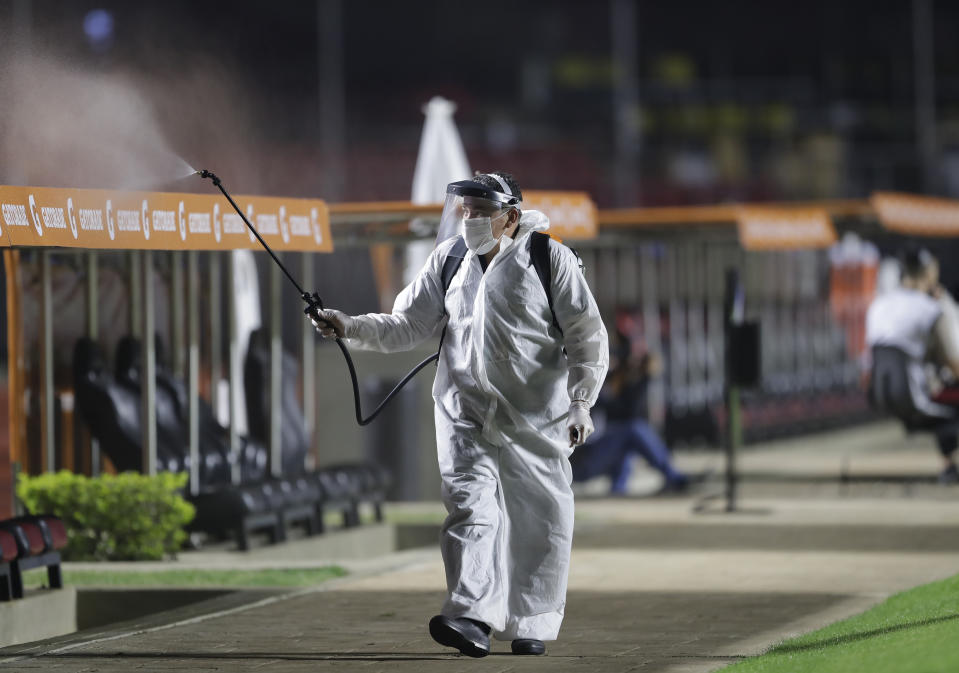 A worker wearing full protective gear disinfects the benches to curb the spread of the new coronavirus, prior a Copa Libertadores soccer match at the Morumbi stadium in Sao Paulo, Brazil, Tuesday, Oct. 20, 2020. (AP Photo/Andre Penner, Pool)