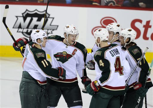 Minnesota Wild's' Miiko Koivu (9), of Finland, celebrates his goal against the Calgary Flames with Zach Parise (11), Clayton Stoner (4), Charlie Coyle (63) and Tom Gilbert during the first period of their NHL hockey game in Calgary, Alberta, Monday, April 15, 2013. (AP Photo/The Canadian Press, Larry MacDougal)