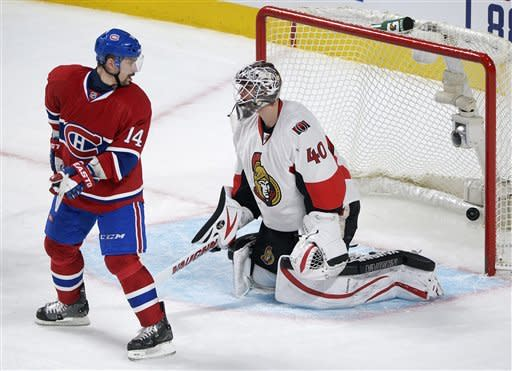 Ottawa Senators goaltender Robin Lehner is scored on by Montreal Canadiens' P.K. Subban, not seen, as Canadiens' Tomas Plekanec looks at the puck in the goal during the second period of an NHL hockey game in Montreal, Wednesday, March 13, 2013. (AP Photo/The Canadian Press, Graham Hughes)