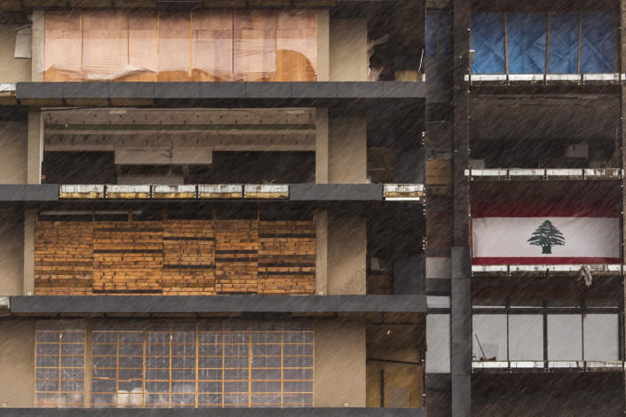 Windows and doors of a building that were damaged in the Aug. 4 explosion in Beirut's port are covered with various materials against the cold and rain, in Beirut, Lebanon, Wednesday, Feb. 17, 2021. Storm Joyce hit late Tuesday with gale force winds registering up to 100 km/h (62 miles/h). (AP Photo/Hassan Ammar)