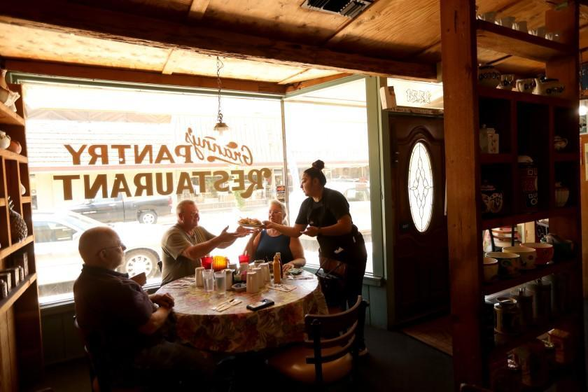 """ATWATER, CA - MAY 27, 2020 - - Waitress Karissa Medina delivers breakfast to Dan Folkner on the first day Granny's Pantry Restaurant reopened to the public in Atwater on May 27, 2020. The city of Atwater in Merced County has declared itself a """"sanctuary city"""" from the state's stay-at-home orders and has been open for business for over a week now. (Genaro Molina / Los Angeles Times)"""