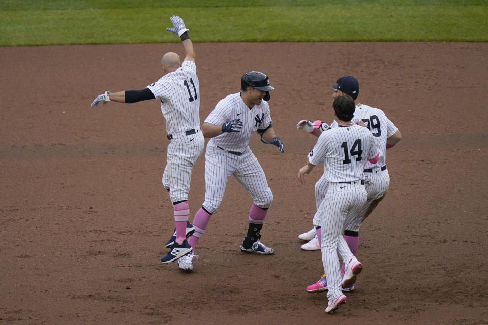 Teammates mob New York Yankees' Giancarlo Stanton, second from left, after he hit a walkoff single during the ninth inning of a baseball game against the Washington Nationals at Yankee Stadium, Sunday, May 9, 2021, in New York. (AP Photo/Seth Wenig)