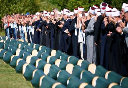 Bosnian Muslims pray in front of coffins during a mass funeral in the village of Hambarine