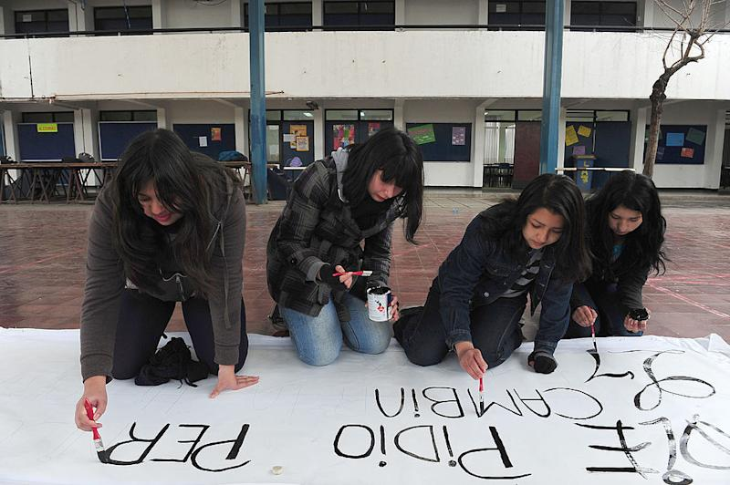 Students from the A-7 public high school for girls paint a banner during a peaceful occupation of the teaching institute in Santiago, on August 14, 2012, during a period of mass student protests. | Claudio Santana/AFP/GettyImages