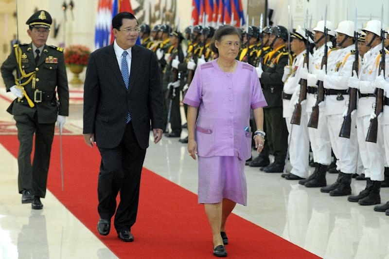 Thai Princess Maha Chakri Sirindhorn and Cambodian Prime Minister Hun Sen walk past honor guards upon her arrival at the Peace Palace in Phnom Penh on February 22, 2016