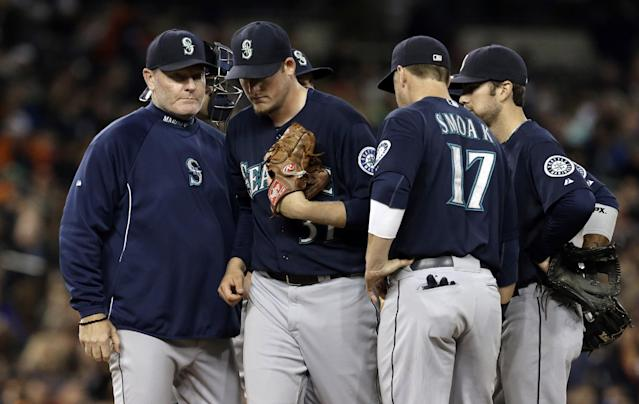 Seattle Mariners manager Eric Wedge, left, pulls starting pitcher Brandon Maurer in the sixth inning of a baseball game against the Detroit Tigers in Detroit, Tuesday, Sept. 17, 2013. (AP Photo/Paul Sancya)