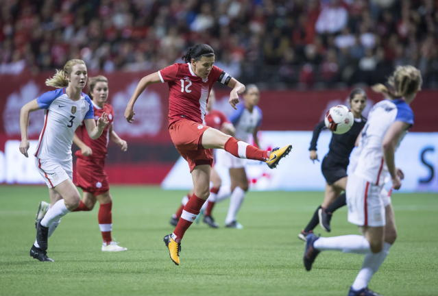 FILE - In this Nov. 9, 2017, file photo, Canada's Christine Sinclair, center, takes a shot on goal as United States' Samantha Mewis (3) watches during the first half of an international friendly soccer match, in Vancouver, British Columbia. The Women's World Cup kicks off Friday, June 7, 2019, in Paris. Sinclair is the most prolific scorer ever in Canadian soccer, and with 181 career goal she's edging closer to former U.S. star Abby Wambach, who holds the all-time international record _ among men or women _ with 184. (Darryl Dyck/The Canadian Press via AP, File)