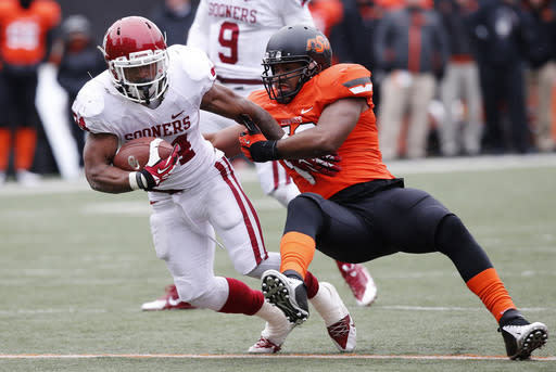 Oklahoma running back Brennan Clay (24) is tackled by Oklahoma State linebacker Ryan Simmons (52) in the second quarter of an NCAA college football game in Stillwater, Okla., Saturday, Dec. 7, 2013. Oklahoma won 33-24. (AP Photo/Sue Ogrocki)