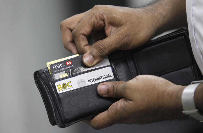 A man pulls out his credit card to make a purchase at a shop