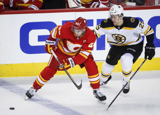 Boston Bruins' Brandon Carlo, right, and Calgary Flames' Sean Monahan chase the puck during NHL hockey action in Calgary, Alberta, Wednesday, Oct. 17, 2018. (Jeff McIntosh/The Canadian Press via AP)
