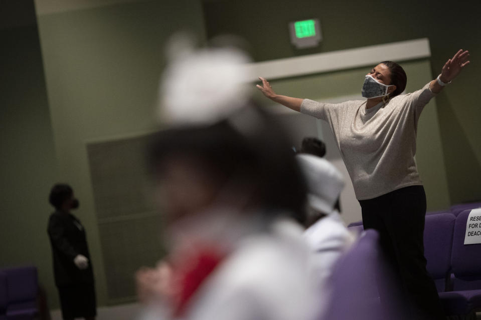 A woman wearing a face mask prays during a church service at the New Horizon International Church, Sunday, Oct. 4, 2020, in Jackson, Miss. In the wake of the coronavirus pandemic, there are carefully enforced mask mandates, multiple disinfectant stations, parishioners who sit 2 or 3 pews apart, cameras to broadcast sermons to people who want to stay at home and pastors who don't let anyone forget the disease is serious. (AP Photo/Wong Maye-E)