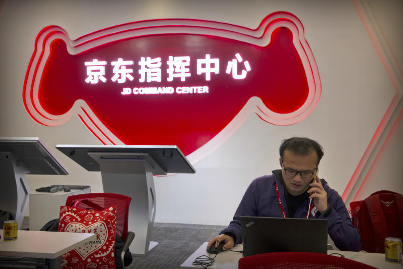 A worker talks on his cellphone as he uses his laptop computer at the command center at the headquarters of e-commerce retailer JD.com in Beijing, Sunday, Nov. 11, 2018. Online shoppers spent more than $14 billion within the first two hours of China's annual buying frenzy on Sunday, once again breaking records as the consumer tradition enters its 10th year. (AP Photo/Mark Schiefelbein)
