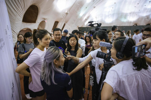 Two-time Grand Slam champion Li Na, left, talks to members of the media at the Sutton East Tennis Club Thursday, July 18, 2019, in New York. Li Na will be inducted into the Tennis Hall of Fame on Saturday, July 20. (AP Photo/Kevin Hagen)