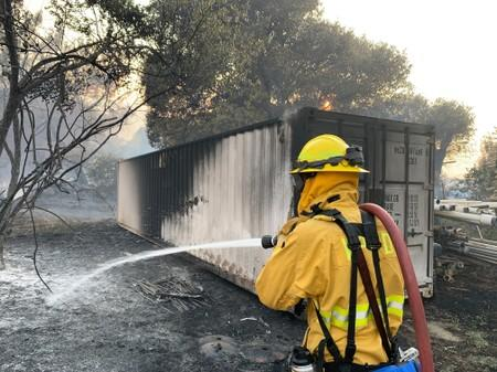 A fireman puts out flames from the Sand Fire in the Capay Valley in California