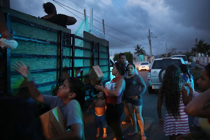 Hurricane survivors receive food and water being distributed by volunteers and municipal police as they deal with the aftermath of Hurricane Maria on Thursday in Toa Baja, Puerto Rico.