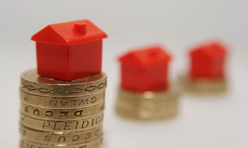Plastic models of houses sitting on a pile of one pound coins