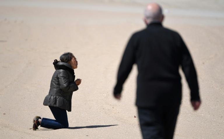 A woman prays on St Kilda Beach in Melbourne as the city begins to reopen after months of coronavirus restrictions