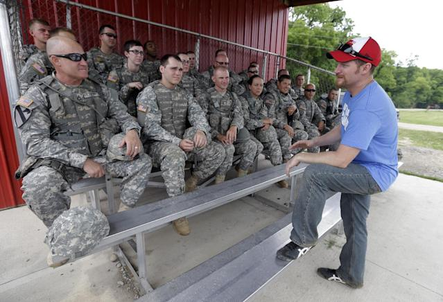 NASCAR driver Dale Earnhardt Jr., talks with soldiers after firing a M4 Rifle at Camp Atterbury Wednesday, July 23, 2014, in Edinburgh, Ind. (AP Photo/Darron Cummings)