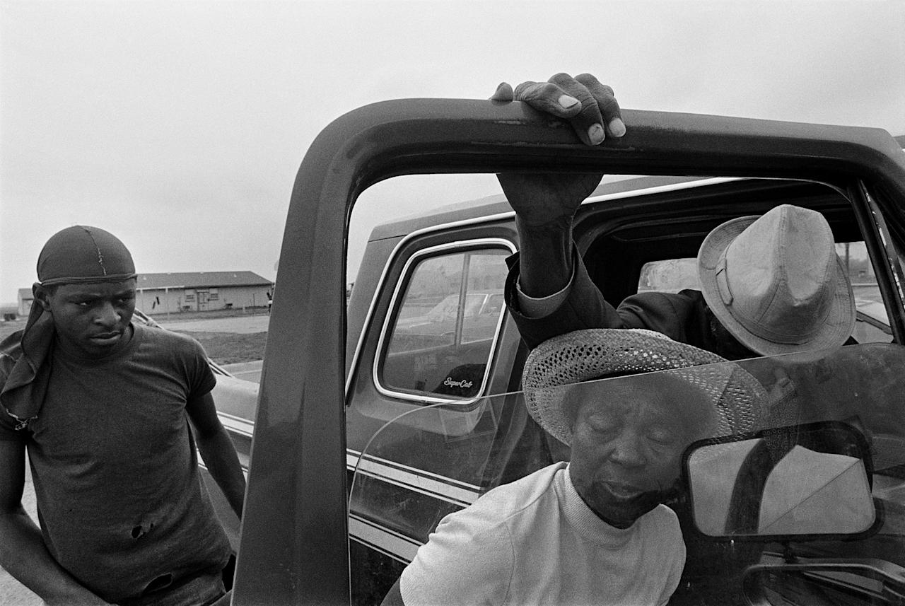 <p>Porter Lee Davis helps her critically ill husband, Mr. Will, from the cab of their pickup truck, 1986. (© Eugene Richards) </p>
