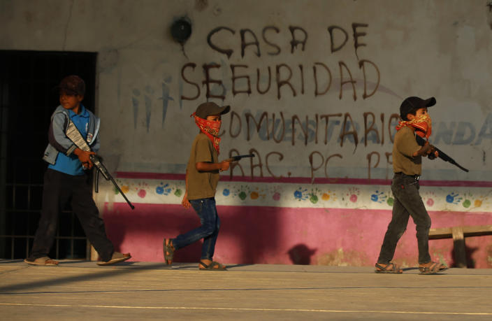 Children train with fake weapons during a display for the media designed to to attract the federal government's attention to the dangers of organized crime their town negotiates daily in Ayahualtempa, Guerrero state, Mexico, Wednesday, April 28, 2021. This long-abandoned and violent region is one of Mexico's poorest and also a key corridor for drug production and transit, especially heroin from opium poppies. (AP Photo/Marco Ugarte)