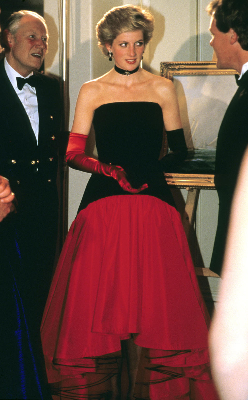 Princess Diana wore one red glove and one back glove while attending the America's Cup Ball at the Grosvenor House hotel in London, on Sept. 1, 1986. The gloves complemented her Murray Arbeid flamenco dress. <em>(Photo by Anwar Hussein/Getty Images)</em>
